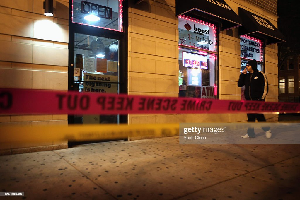 A store owner smokes a cigarette outside his store where two men were shot in the Old Town neighborhood on January 8, 2013 in Chicago, Illinois. Tyshawn Blanton, 31, died as a result of the shooting and a 20-year-old man who was shot in the back was taken to the hospital in serious-to-critical condition. Blanton's murder was at least the 14th murder in the city this year. The Old Town neighborhood was selected last month by Realtor.com as 2012's hottest neighborhood in the country. Today Vice President Joe Biden will be meeting with victims' groups and gun-safety organizations at the White House in his effort to develop proposals to curb gun violence following the Sandy Hook school shooting in Newtown, Connecticut. Tomorrow he is expected to meet with the NRA.