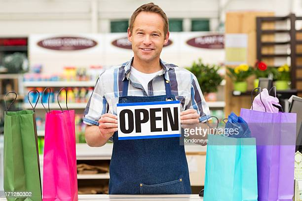 Store owner with an open sign