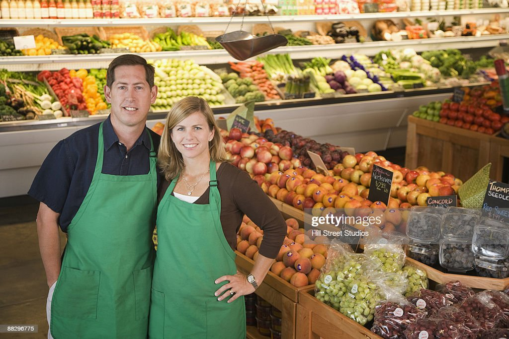 Store owners posing in produce section : Stock Photo