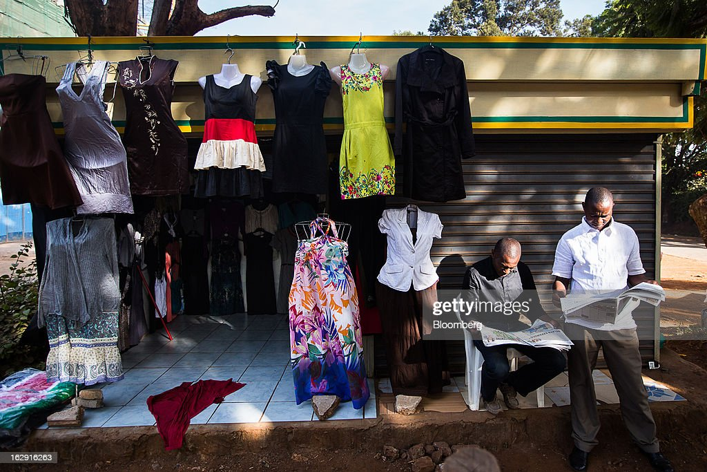 Store owners read papers while waiting for customers outside a clothes store in Nairobi, Kenya, on Friday, March 1, 2013. Next week's presidential vote will be the first since disputed elections in 2007 triggered ethnic fighting in which more than 1,100 people died and another 350,000 fled their homes. Photographer: Trevor Snapp/Bloomberg via Getty Images