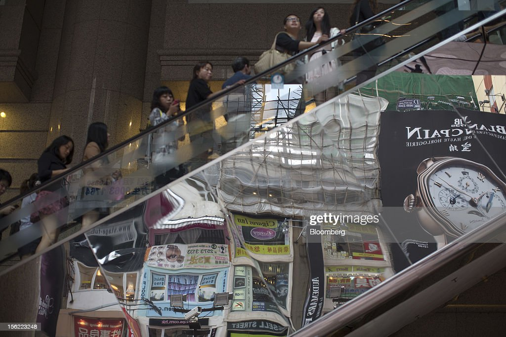 Store signs are reflected on the side of escalators at Times Square shopping mall, operated by Wharf (Holdings) Ltd., in the Causeway Bay district of Hong Kong, China, on Friday, Nov. 9, 2012. Wharf (Holdings) Ltd. is controlled by the family of billionaire Chairman Peter Woo. Photographer: Jerome Favre/Bloomberg via Getty Images