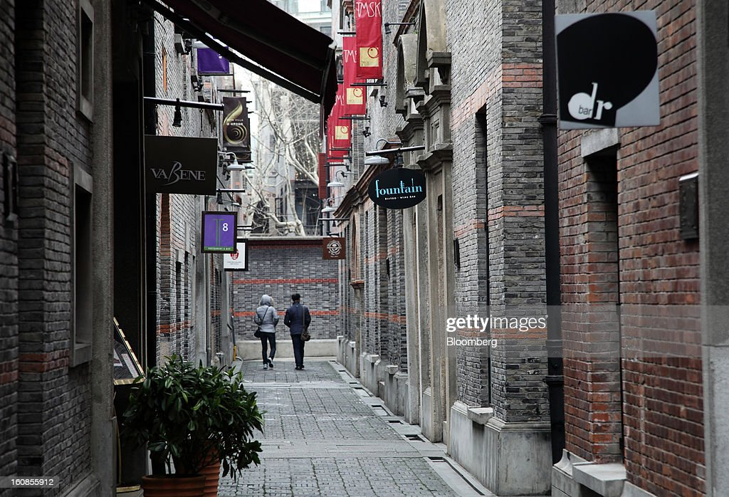 Store signs hang in a lane in the Shanghai Xintiandi precinct, a project developed by Shui On Land Ltd., in Shanghai, China, on Wednesday, Feb. 6, 2013. China's economic growth accelerated for the first time in two years as government efforts to revive demand drove a rebound in industrial output, retail sales and the housing market. Photographer: Tomohiro Ohsumi/Bloomberg via Getty Images