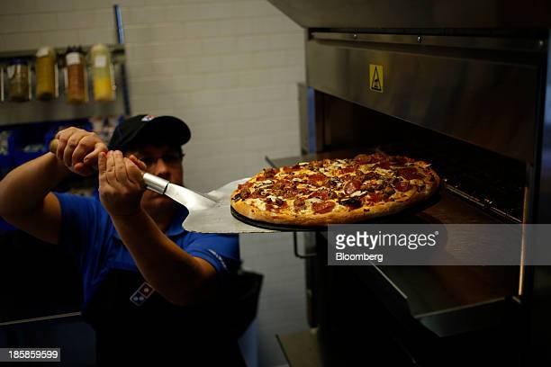 Store supervisor Kim Hopkins pulls a pizza from the oven during lunch hour at a Domino's Pizza Inc location in Murray Kentucky US on Thursday Oct 24...