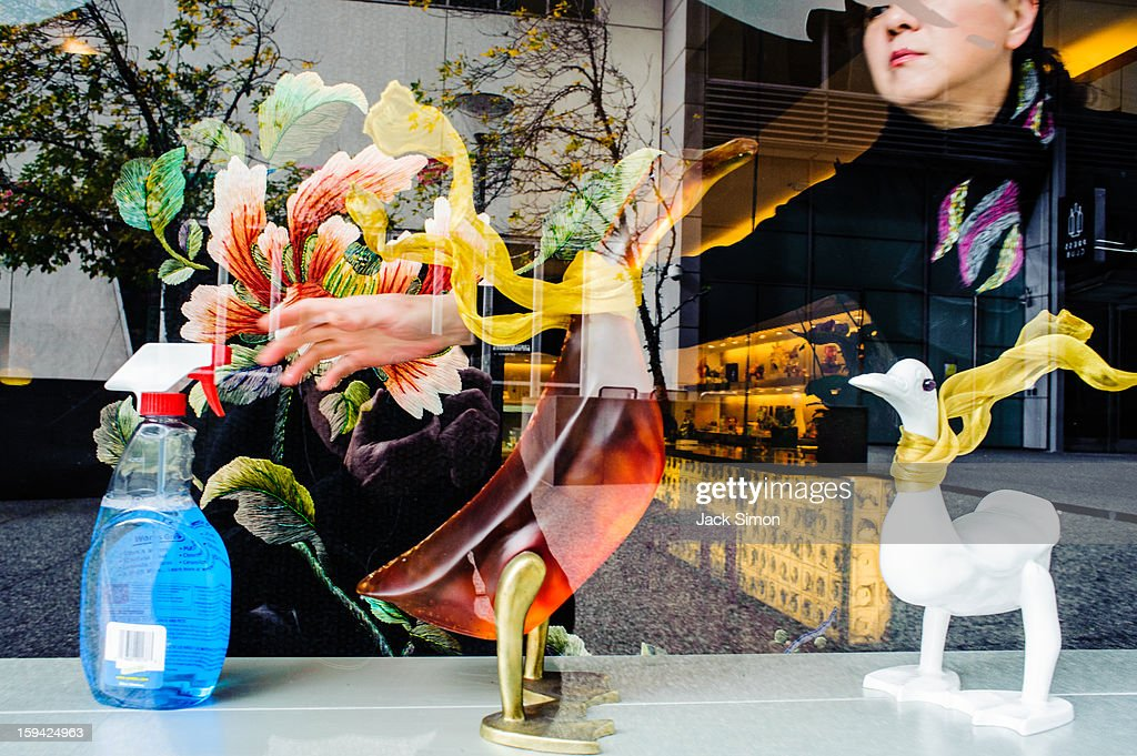 CONTENT] Store window, woman reaching for cleaning fluid which resembles glass birds for sale.