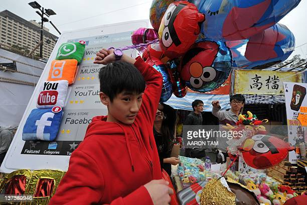 A store worker moves balloons with various cartoon characters on them past a large poster with iPhone apps cushions on it at the Hong Kong Chinese...
