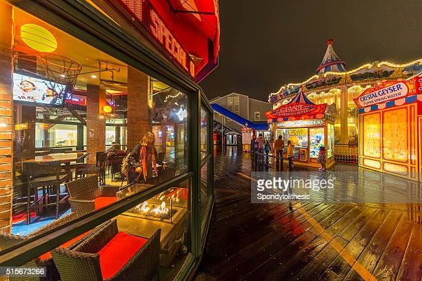 Storefronts at Pier 39 at night after heavy rain