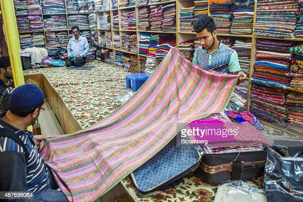 A storekeeper displays a pashmina shawl to a customer at a store in Srinigar Jammu and Kashmir India on Tuesday Aug 25 2015 Pashmina goats are no...