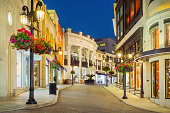 Photo of Rodeo Drive with illuminated stores in Beverly Hills, Los Angeles, California, USA at twilight blue hour.
