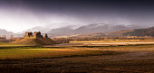 A rain storm in Strathspey in the Cairngorm Mountains of the Scottish Highlands, The ruins of Ruthven Barracks stand on a hill in the middle of the valley wetlands.
