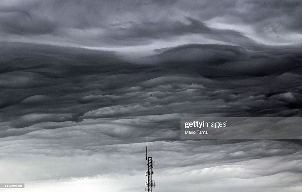 A storm cloud passes over a communications tower following a thunderstorm five days after a massive tornado after a massive tornado passed through...