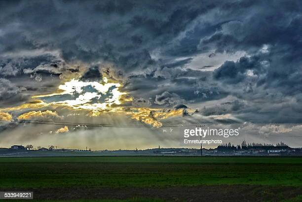 Storm clouds and sunbeams over village