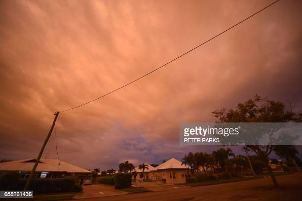 Storm clouds gather in the town of Ayr in far north Queensland as Cyclone Debbie approaches on March 27 2017 Thousands of people including tourists...