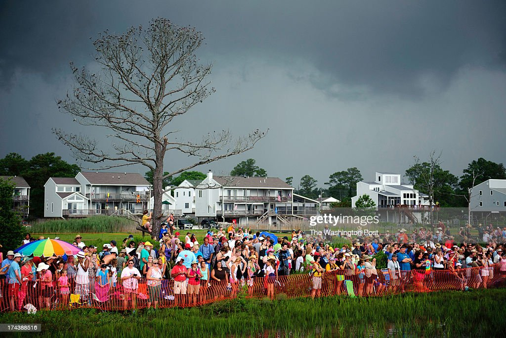 Storm clouds gather over spectators of the 88th Annual Pony Swim in Chincoteague Island, VA, on July 24, 2013. The ponies are auctioned to benefit the Chincoteague Volunteer Fire Company.