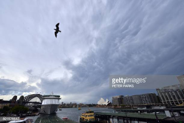 Storm clouds gather over Sydney Harbour in Sydney on December 16 2015 Sydney was smashed by a tornadolike storm with hail as big as golf balls and...