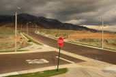 Storm clouds hover near unfinished home lots during a break between storms after the dwindling new home sales market brought construction to a halt...