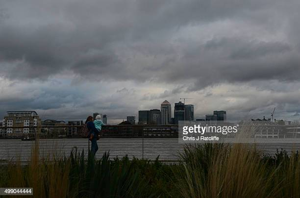 Storm clouds loom over the financial district Canary Wharf as a woman and her child stand on the bank of the Thames in Greenwich on November 27 2015...