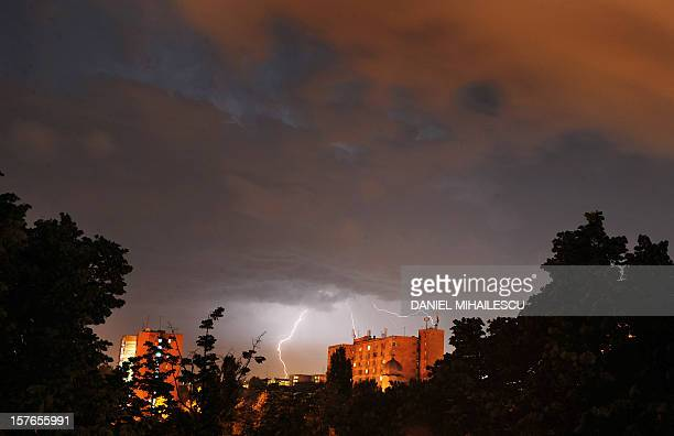 Storm clouds over a residential area in Bucharest are illuminated by lightning and city lights on May 15 2009 AFP PHOTO / DANIEL MIHAILESCU