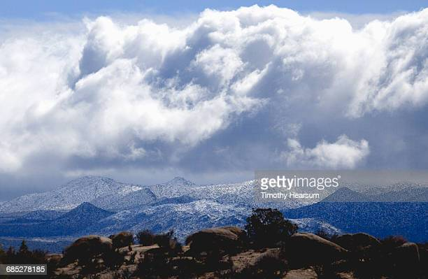 Storm clouds over snow covered mountains