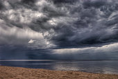 Dark Storm clouds over the sea with light beaming through