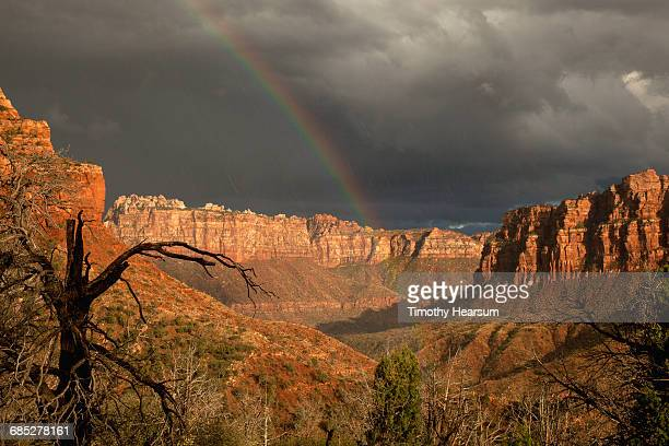 Storm clouds, rainbow over sunny mountains