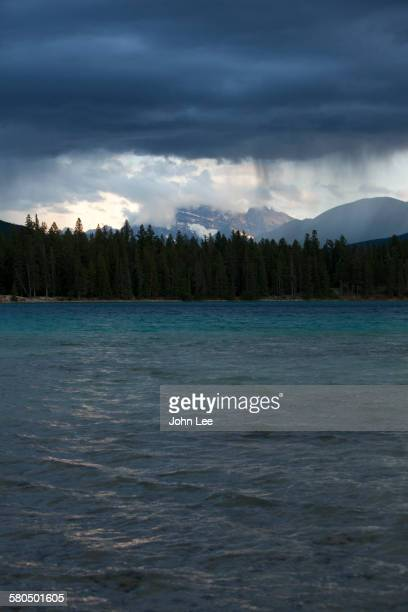 Storm clouds raining over lake