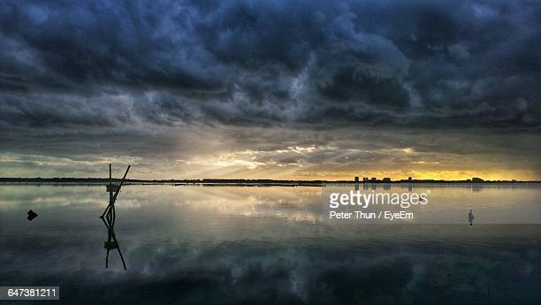 Storm Clouds Reflecting In Sea During Sunset