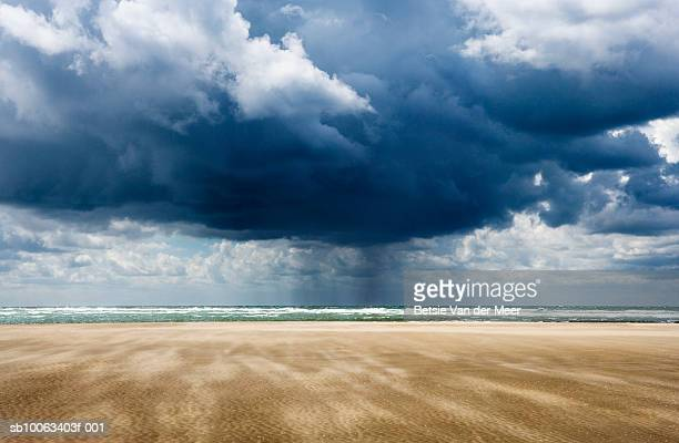 Storm over sea, sandy beach in foreground