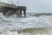 An incoming storm causes massive surf and storm surge to crash into a concrete beach pier.