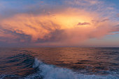 Dramatic colorful clouds at sunset hovering over the sea