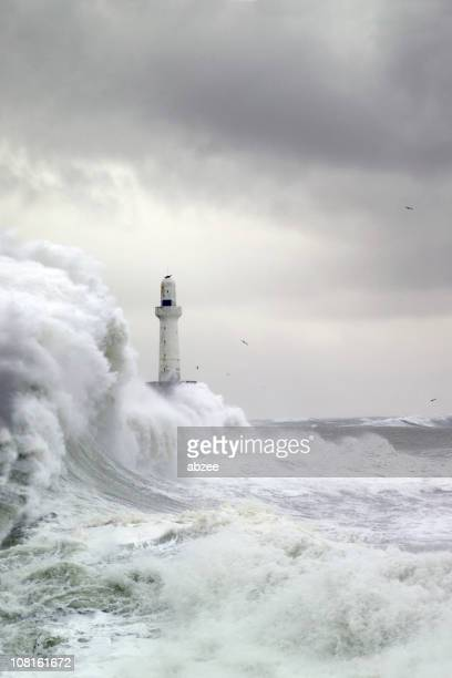 Stormy sea and high waves crashing near a light house