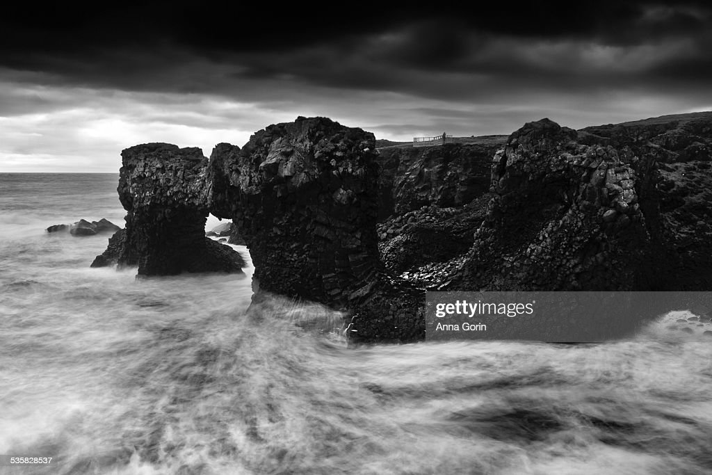 Stormy seas and natural arch in grayscale, Iceland