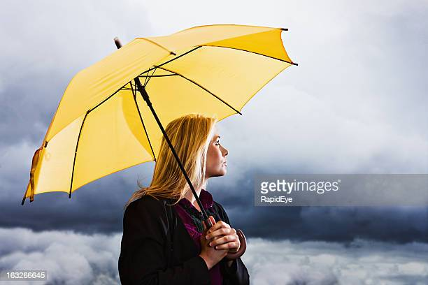 Stormy weather: wistful blonde with yellow umbrella waits out thunderstorm
