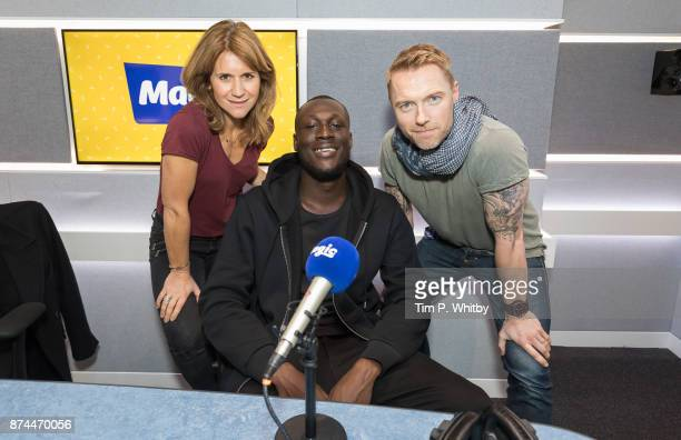 Stormzy poses for a photo with presenters Harriet Scott and Ronan Keating during a visit to the Magic FM Studio's on November 15 2017 in London...