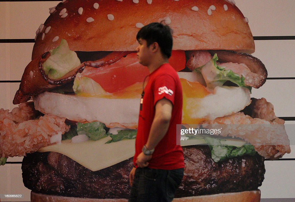 Asia-food-lifestyle-Malaysia-Singapore-SKorea-Australia, FEATURE by Shannon Teoh This picture taken on January 5, 2013 shows a worker walking past a pork burger advertisement poster inside a restaurant in Kuala Lumpur. As a Hindu who cannot eat beef, Tashny Sukumaran satisfies her meat cravings with pork burgers, a new food passion she discovered via her native Malaysia's vibrant food-blogging, or 'flogging' scene. AFP PHOTO / MOHD RASFAN