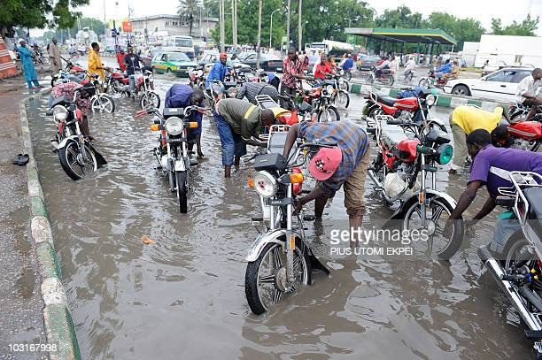 un an après une insurrection islamiste des interrogations Public transport motorcylists wash their motocycles on the flooded road from a rainfall in...