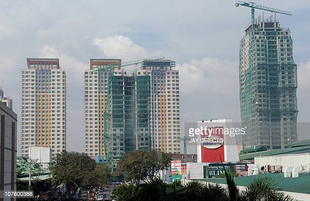 Philippineseconomypropertylabour' by Mynardo MacaraigAlmost completed high rise condominiums in front of a shopping center in Quezon City suburban...