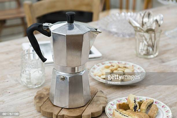 Stove top coffee pot with plates of baked good on dining table