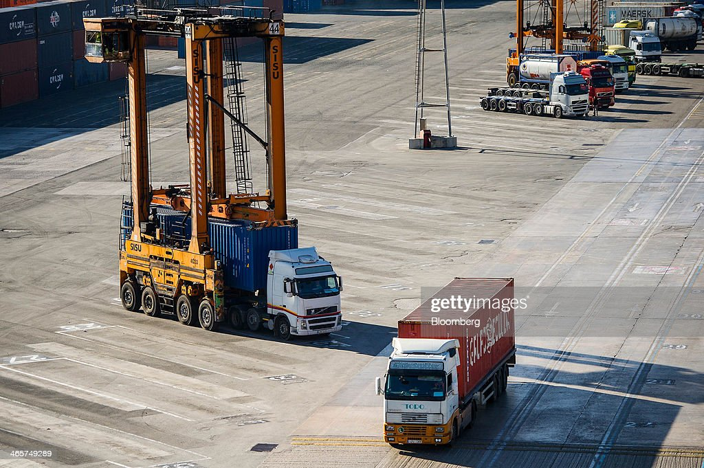A straddle carrier loads a shipping container onto a waiting truck at the commercial port in Barcelona, Spain, on Wednesday, Jan. 29, 2014. Government bonds in Europe's most-indebted countries rallied in the first three weeks of the year on signs the debt crisis that pushed those nations' borrowing costs to euro-era records had abated. Photographer: David Ramos/Bloomberg via Getty Images