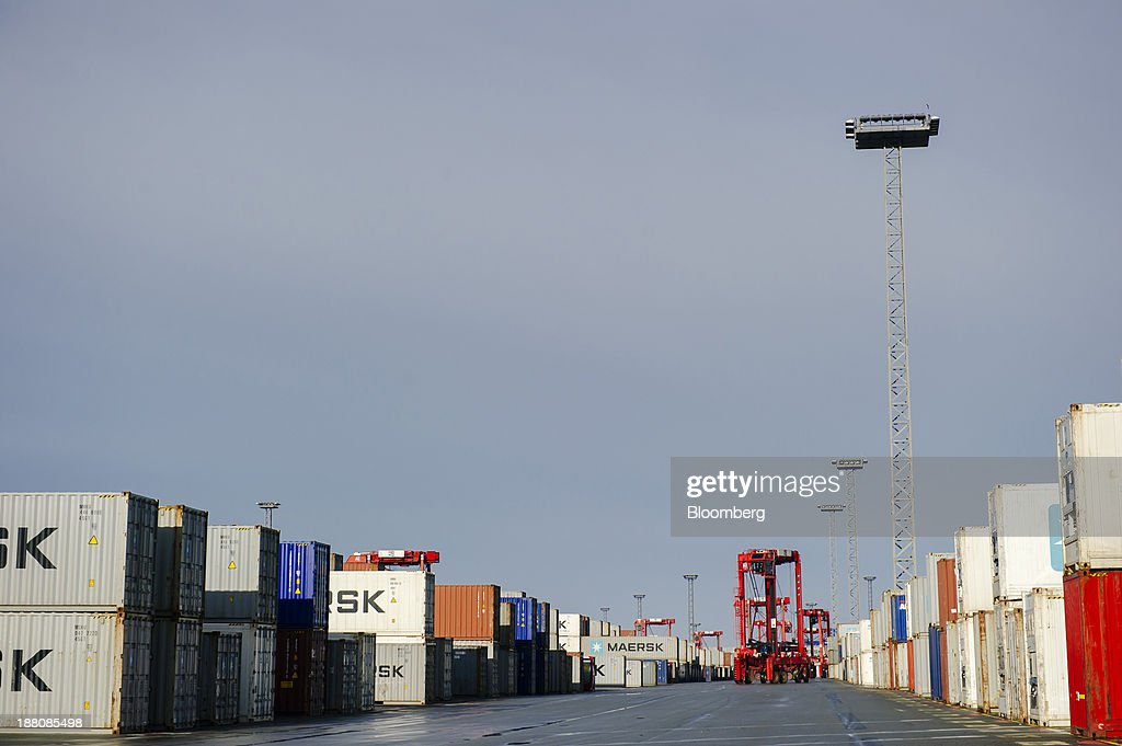 Straddle carriers arrange shipping containers on the dockside during loading operations for the Maersk Mc-Kinney Moeller Triple-E Class container ship, operated by A.P. Moeller-Maersk A/S, in the Port of Bremerhaven in Bremerhaven, Germany, on Monday, Nov. 11, 2013. A.P. Moeller-Maersk A/S's container-shipping line, the world's largest, reported an 11 percent increase in third-quarter profit after cost cuts countered a decline in freight rates. Photographer: Kristian Helgesen/Bloomberg via Getty Images