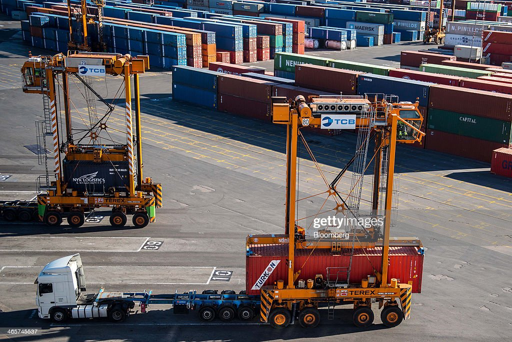 Straddle carriers load shipping containers onto waiting trucks on the quayside at the commercial port in Barcelona, Spain, on Wednesday, Jan. 29, 2014. Government bonds in Europe's most-indebted countries rallied in the first three weeks of the year on signs the debt crisis that pushed those nations' borrowing costs to euro-era records had abated. Photographer: David Ramos/Bloomberg via Getty Images