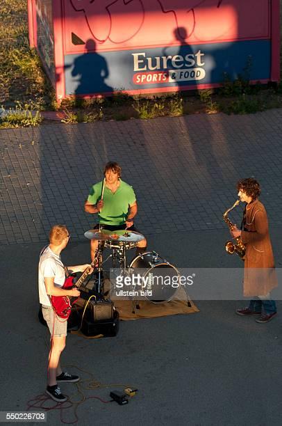 Straßenmusiker im letzten Licht der Sonne unter der Brücke am SBahnhof Warschauer Straße in BerlinFriedrichshain