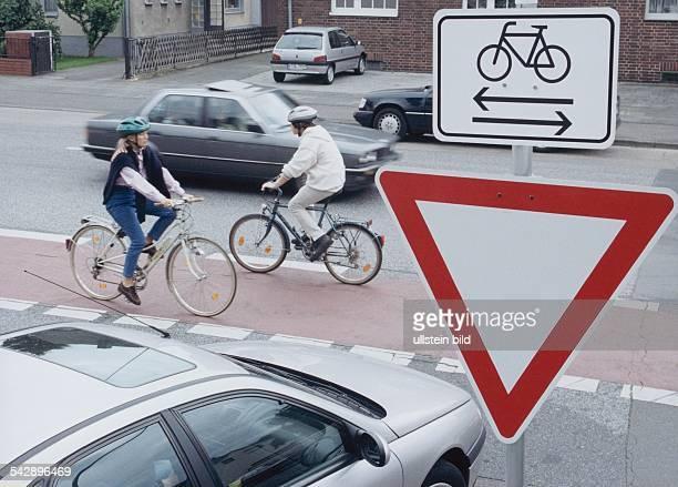 Straßenschild 'Vorfahrt beachten' mit Zusatzschild Das Zusatzschild mit einem abgebildeten Fahrrad und zwei entgegengesetzten Pfeilen darunter weist...