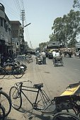 Straßenszene aus Meerut in Uttar Pradesh einer typischen Kleinstadt im Norden Indiens Eine Fahrradrikscha parkt im Vordergrund Lastwagen und...