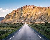 Straight asphalt road with mountain landscape against blue sky in Lofoten, Norway