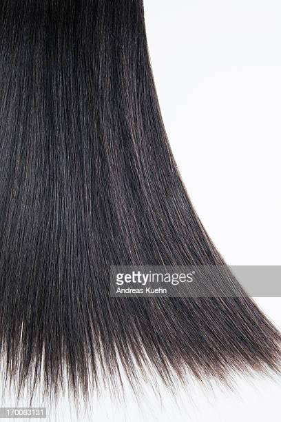 Straight dark brown hair on a white background.