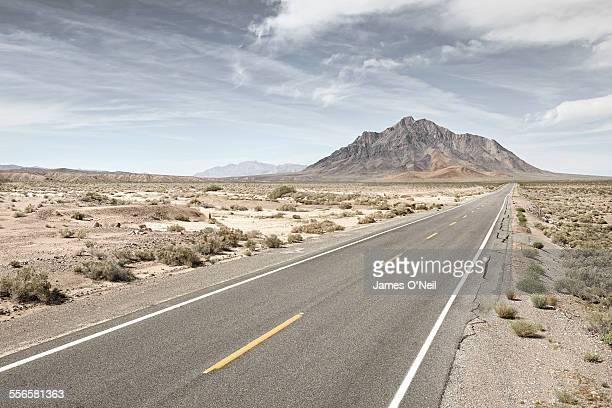 straight road in desert with distant mountain.