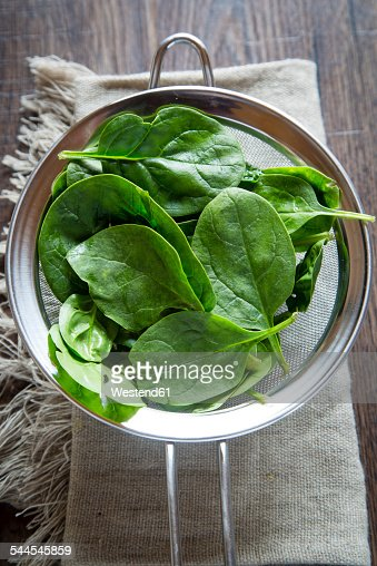 Strainer of fresh baby leaf spinach on cloth and wood