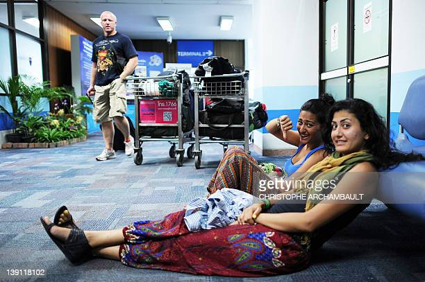 A stranded Air Australia passenger gives a thumb down as they wait with their luggage at Phuket international airport after their flight was...
