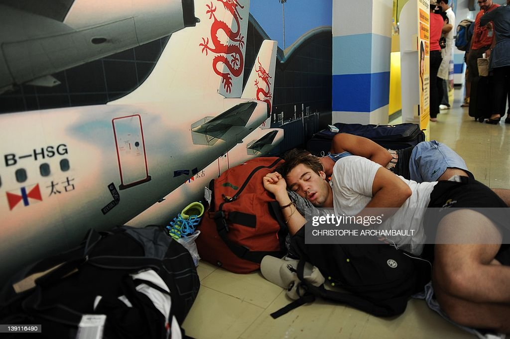 Stranded Air Australia passengers sleep with their luggage at Phuket international airport after their flight was cancelled on February 17, 2012. Budget carrier Air Australia collapsed on February 17, stranding thousands of passengers as its domestic flights and international services to Honolulu, Bali and Phuket were all grounded. AFP PHOTO/Christophe ARCHAMBAULT