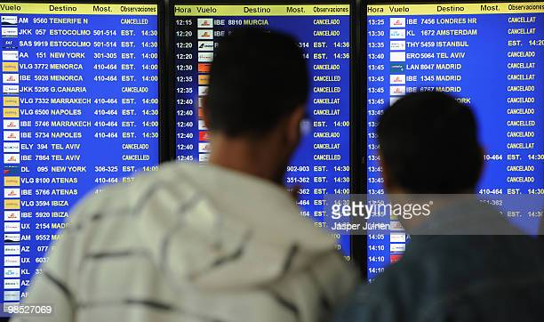 Stranded airline passengers look at a departure information screen showing cancelled flights at El Prat international airport on April 18 2010 in...